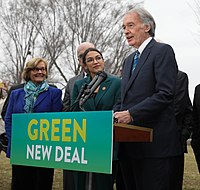 The Green New Deal, championed by Democrats upon their new House majority, was proposed by Senator Ed Markey (speaking) and Representative Alexandria Ocasio-Cortez (next to him, February 7, 2019