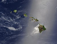 A true-color satellite view of Hawaii shows that most of the islands' vegetation is on their northeast sides, which face the wind. The silver glow indicates calmer waters downwind.