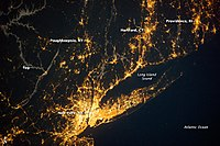 Nocturnal view of the New York City metropolitan area, the world's most brightly illuminated conurbation and largest urban landmass. Long Island extends 120 miles eastward from Manhattan, the central core of the conurbation.