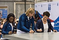 Biles signs a 35-ton steel plate alongside Katie Ledecky and NNS president Jennifer Boykin to signal the start of construction of the