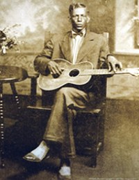 Charley Patton, one of the originators of the Delta blues style, playing with a pick or a bottleneck slide