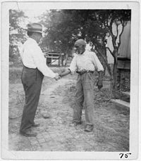 """John Lomax (left) shaking hands with musician """"Uncle"""" Rich Brown in Sumterville, Alabama"""