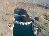 An aerial view of Glen Canyon Dam from upstream, showing the spillways to lower left and right, the Glen Canyon Bridge and the electric switchyard to the right of the bridge.