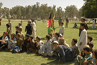 Local children watching a football match at the playground of Ahmad Shah Baba High School.