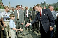 Reagan greets a young boy while touring Red Square with Gorbachev during the Moscow Summit, 31 May 1988