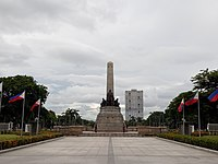 View of the Rizal Monument in Rizal Park with the controversial Torre de Manila looming in the background.