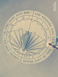 "The rim of the sundial contains a poem reading ""Time flies suns rise and shadows fall let it pass by love reigns forever over all""."