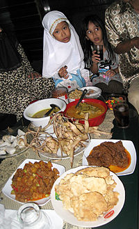 An Indonesian family celebrating lebaran with various culinary dishes specific to this holiday