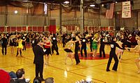 Intermediate level international-style Latin dancing at the 2006 MIT ballroom dance competition. A judge stands in the foreground.