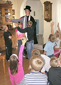 """Amateur magician performing """"children's magic"""" for a birthday party audience"""