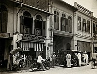 An arcade of shophouses with a road sweeper at work in the street of Kuala Lumpur, c.1915–1925.