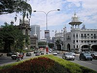 The Kuala Lumpur Railway Station (right) contrasts with a Keretapi Tanah Melayu (left) Administration Building darker, similarly Mughal-styled building. Both designed by A. B. Hubback