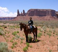 A young Navajo boy on horseback in Monument Valley. The Navajo Nation includes much of the Four Corners area, including the valley, used in many western movies.
