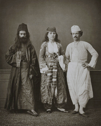 Traditional costumes of (from right to left) a Christian resident of Famagusta, a Christian woman of Famagusta, and an Orthodox monk of the Monastery of Tchiko, near Lefka. Photographed in Cyprus in 1873.