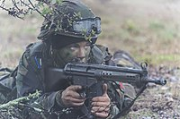 A Portuguese female soldier in position, with her H&K G3 rifle, during a field exercise