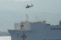 Helicopters transfer injured earthquake victims to hospital ship USNS Comfort off the coast of Haiti