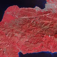 Tiny dots of white against the plant-covered landscape (red in this image) are possible landslides, a common occurrence in mountainous terrain after large earthquakes. The Enriquillo-Plantain Garden fault zone runs along the two linear valleys at the top of the image