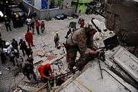 A USAF pararescueman searching through demolished buildings in Port-au-Prince for survivors