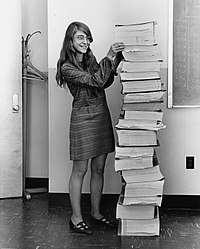 Margaret Hamilton next to a stack of code she and her team wrote for the Apollo Mission computers.