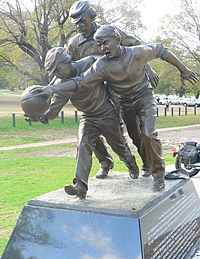 """Statue next to the Melbourne Cricket Ground on the approximate site of the 1858 football match between Melbourne Grammar and Scotch College. Tom Wills is depicted umpiring behind two young players contesting the ball. The plaque reads that Wills """"did more than any other person – as a footballer and umpire, co-writer of the rules and promoter of the game – to develop Australian football during its first decade."""""""