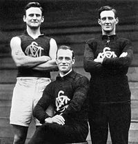 """South Melbourne's renowned ruck combination of the 1920s, left to right: Mark Tandy, Fred Fleiter and Roy Cazaly. Fleiter coined the phrase """"Up there, Cazaly!"""" as a signal that he had cleared the way for Cazaly to leap for the ball. It was used as a battle cry by Australian soldiers during World War II, and inspired Mike Brady's 1979 Australian football anthem of the same name."""