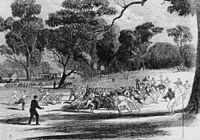 Engraving of a football match at the Richmond Paddock, 1866. The MCG and its first pavilion are visible in the background, as are kick-off posts, the forerunner of today's behind posts.