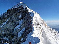 Looking up along the southern ridgeline, the face of the Hillary Step is visible. The top of the South-West face is on the left in shadow, and in the light to the right is the top of the East/Kangshung face. In 2016 and 2017 there were serious reports that the Hillary Step was changed, which triggered a big discussion in the climbing community. (2010 photo)