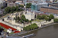 The Tower of London from The Shard. The River Thames is to the south. The outer curtain walls were erected in the 13th century. In the moat is the art installation Blood Swept Lands and Seas of Red.