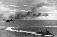 HMS Prince of Wales (left, front) and HMS Repulse (left, rear) under attack by Japanese aircraft. A destroyer is in the foreground.