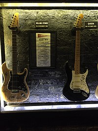 Queen guitar (right, next to a Rolling Stones guitar) at the Cavern Club in Liverpool, marking a 31 October 1970 Queen concert at the venue