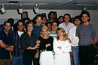 Part of the writing staff of The Simpsons in 1992. Back row, left to right: Mike Mendel, Colin A. B. V. Lewis (partial), Jeff Goldstein, Al Jean (partial), Conan O'Brien, Bill Oakley, Josh Weinstein, Mike Reiss, Ken Tsumura, George Meyer, John Swartzwelder, Jon Vitti (partial), CJ Gibson, and David M. Stern. Front row, left to right: Dee Capelli, Lona Williams, and unknown
