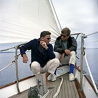 """Lawford sailing with his brother-in-law President John F. Kennedy aboard the yacht """"Manitou"""", a former USCG training vessel that was used as a """"floating White House', off the coast of Johns Island, Maine, August 12, 1962"""