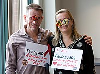"""People wearing AIDS awareness signs. on the left: """"Facing AIDS a condom and a pill at a time""""; on the right: """"I am Facing AIDS because people I ♥ are infected."""""""