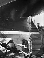 RMS Olympic's rudder with central and port wing propellers; for scale note the man at the bottom of the photo.