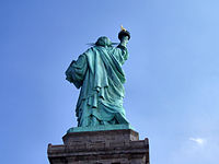 Liberty is depicted with a raised right foot, showing that she is walking forward
