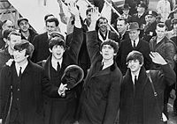 Lennon, McCartney, Harrison and Starr arrive at Kennedy International Airport to screaming fans, February 1964.