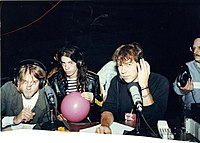 Cobain (left) and Grohl (middle) being interviewed by WFNX's Kurt St. Thomas (right) in 1991