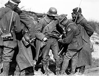 """Australian soldiers searching German prisoners of war for """"souvenirs"""" in October 1918. Australian soldiers generally treated captured Germans humanely, but routinely stole their belongings."""