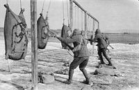 Three Australian soldiers practising bayonet attacks while wearing gas masks in England during 1916 or 1917