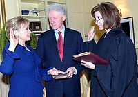 Associate Judge Kathryn Oberly of the D.C. Court of Appeals administers the oath of office of secretary of state to Hillary Rodham Clinton as her husband Bill Clinton holds the Bible