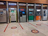 Social distance stickers placed on the floor in the ATM part of a shopping mall.