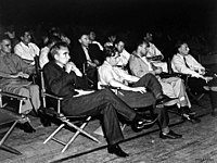 Physicists at a Manhattan District-sponsored colloquium at Los Alamos on the Super in April 1946. In the front row are (left to right) Norris Bradbury, John Manley, Enrico Fermi and J. M. B. Kellogg. Robert Oppenheimer, in dark coat, is behind Manley; to Oppenheimer's left is Richard Feynman. The Army officer on the left is Colonel Oliver Haywood.