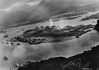Photograph from a Japanese plane of Battleship Row at the beginning of the attack. The explosion in the center is a torpedo strike on the . Two attacking Japanese planes can be seen: one over the and one over the Naval Yard.