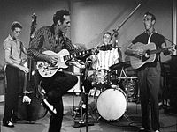 """Carl Perkins (2nd from left) performing """"Glad All Over"""" with (left to right) Clayton Perkins, W.S. """"Fluke"""" Holland, and Jay Perkins in the movie Jamboree"""