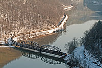 A long CSX coal train of empty hoppers crosses the New River as seen from Hawks Nest State Park