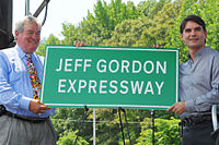 Secretary of the North Carolina Department of Transportation Gene Conti and Gordon unveiling a sign for the Jeff Gordon Expressway