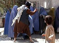 Member of the Taliban's religious police beating an Afghan woman in Kabul on August 26, 2001. State violence against women is a form of discrimination.