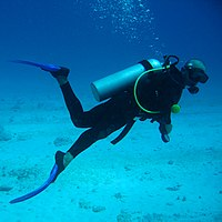 Scuba diver with face mask, fins and underwater breathing apparatus