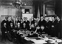 At the first Solvay Conference (1911), Curie (seated, second from right) confers with Henri Poincaré; standing, fourth from right, is Rutherford; second from right, Einstein; far right, Paul Langevin.
