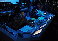 U.S. Navy officers aboard the aircraft carrier monitor defense systems during early 2010s maritime security operations exercises